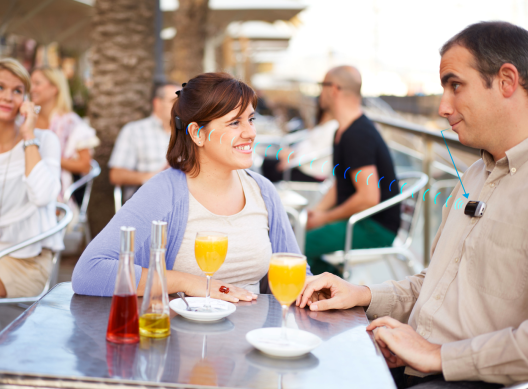 Baha user Monica in a conversation with her husband, who is wearing the Mini Microphone, at an outdoor café in Barcelona